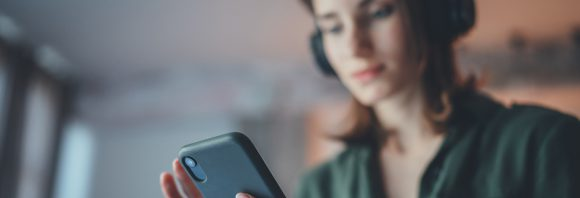 Young handsome girl relaxing at modern home, wearing casual clothes, playing music on smartphone and listening audio books in wireless headphones.Blurred background.
